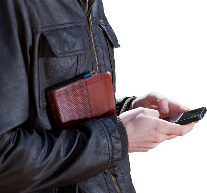 person in leather jacket with phone and bible